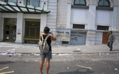 A woman photographing, with her mobile phone, the material landscape that followed a political demonstration against austerity measures in June 2011, near Syntagma Square